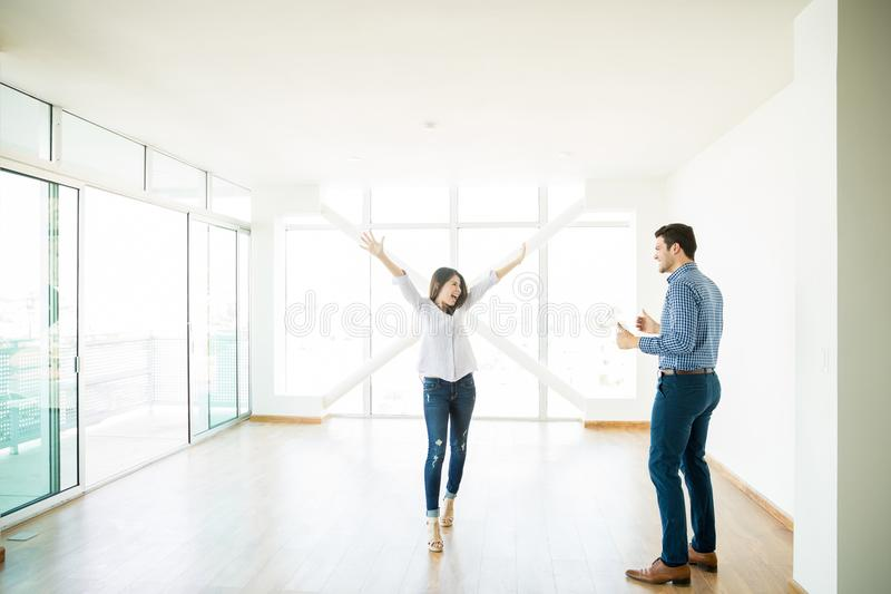 Man Looking At Excited Woman With Arms Raised In New House. Mid adult men looking at excited women with arms raised in new house stock photography