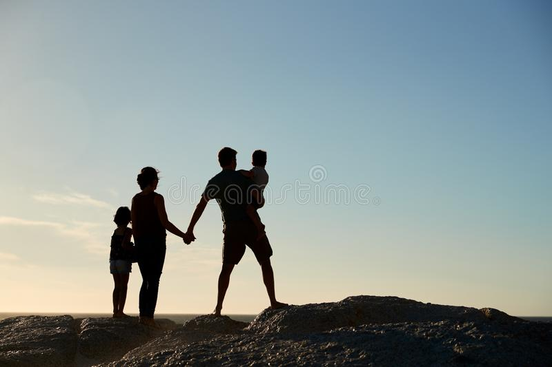 Mid adult parents and two pre-teen children standing on beach admiring view, full length, silhouette royalty free stock photo