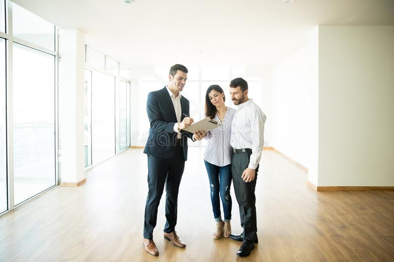 Realtor Explaining Agreement To Couple In New Apartment. Mid adult realtor explaining agreement to couple in new apartment stock photography