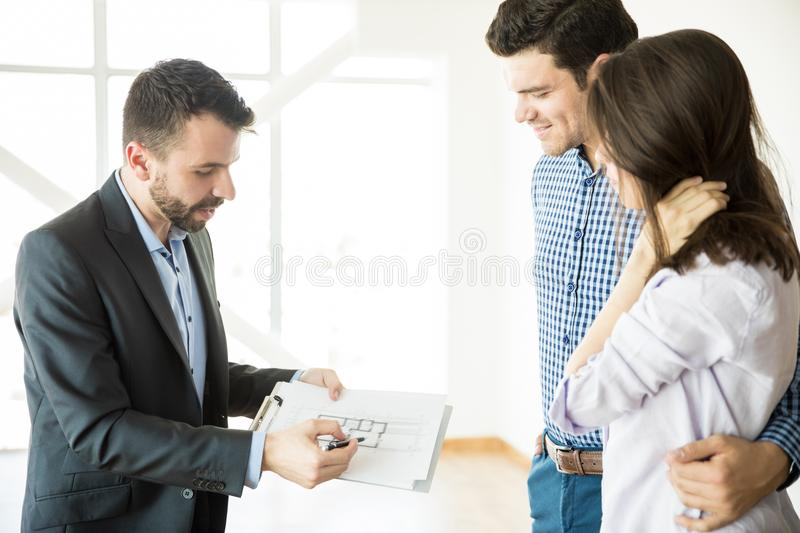 Realtor Showing Blueprint To Couple In New Apartment. Mid adult realtor showing blueprint to couple in new luxury apartment royalty free stock photo