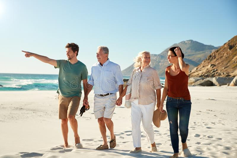 Mid adult and senior white couples walking on a beach together talking, full length, close up stock image