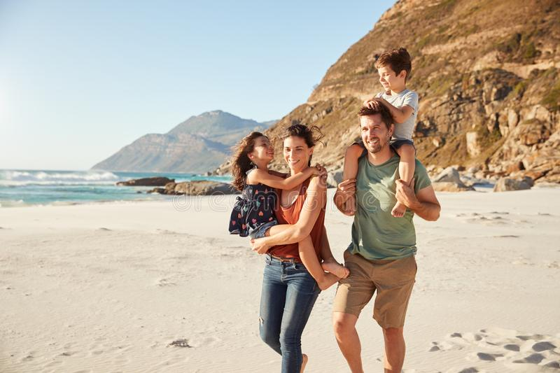 Mid adult white couple walking along on a beach carrying their children during a family holiday royalty free stock image
