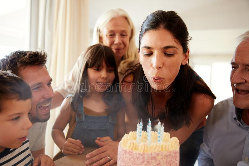 Mid adult white woman blowing out candles on birthday cake watched by her family, close up. Mid adult white women blowing out candles on birthday cake watched by royalty free stock photography