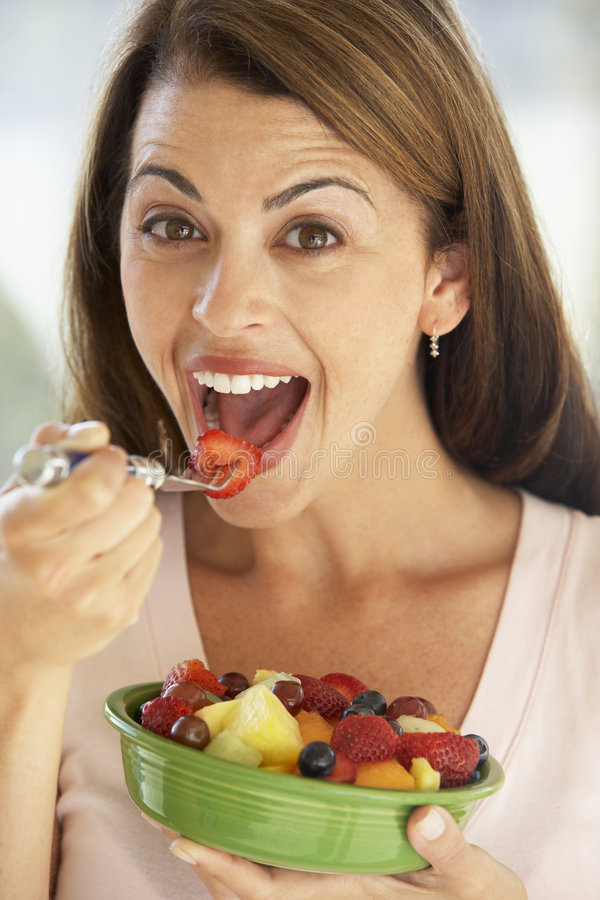 Mid Adult Woman Eating A Fresh Fruit Salad Royalty Free Stock Images