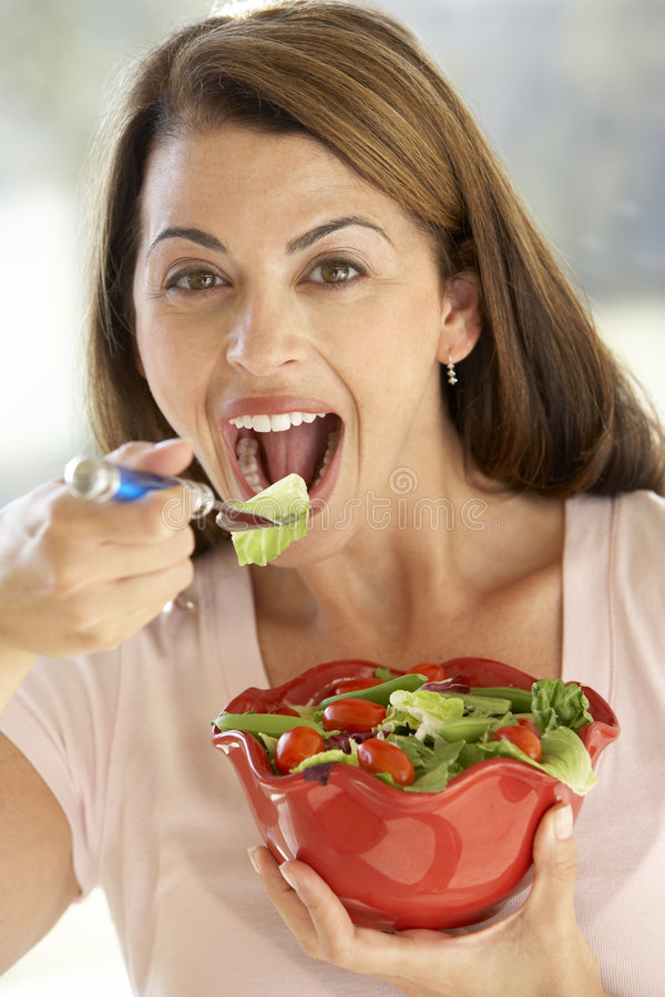 Mid Adult Woman Eating A Fresh Green Salad stock photo