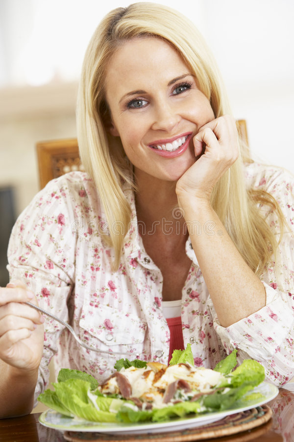 Mid Adult Woman Eating A Healthy Meal. Smiling At The Camera royalty free stock image