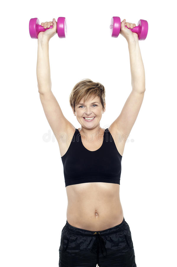 Mid adult woman holding dumbbells over head royalty free stock images
