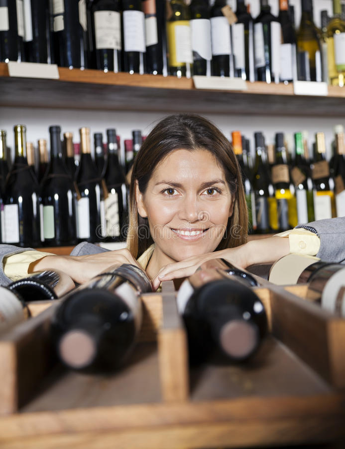 Mid Adult Woman Leaning On Wine Rack In Shop. Portrait of confident mid adult woman leaning on wine rack in shop royalty free stock photo