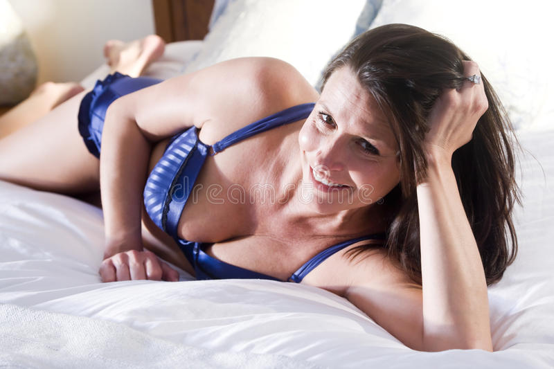 Mid-adult woman in lingerie relaxing on bed