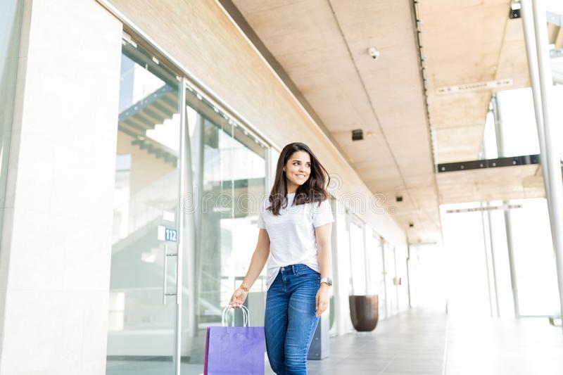Woman Walking With Paper Bags In Shopping Mall royalty free stock photography