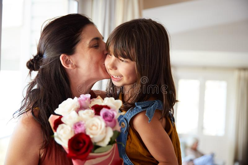 Mid adult woman kissing her daughter, who�s given her a bunch of flowers on her birthday, close up. Mid adult women kissing her daughter, who�s given stock images