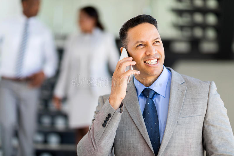 Mid age business executive. Modern mid age business executive talking on cell phone stock photo