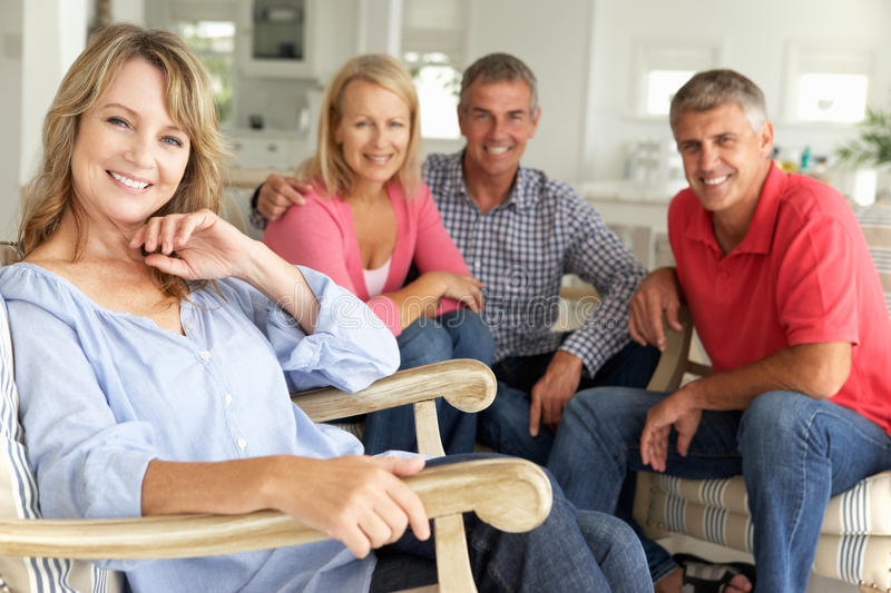 Mid age couples relaxing together at home royalty free stock photography