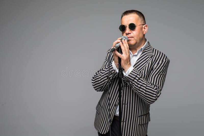 The mid age Showman interviewer with emotions. Young elegant mature man holding microphone against white background. Showman conce stock photography