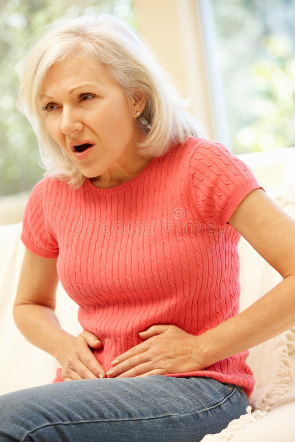 Mid age woman with stomach ache. Mid age women with stomach ache stock images