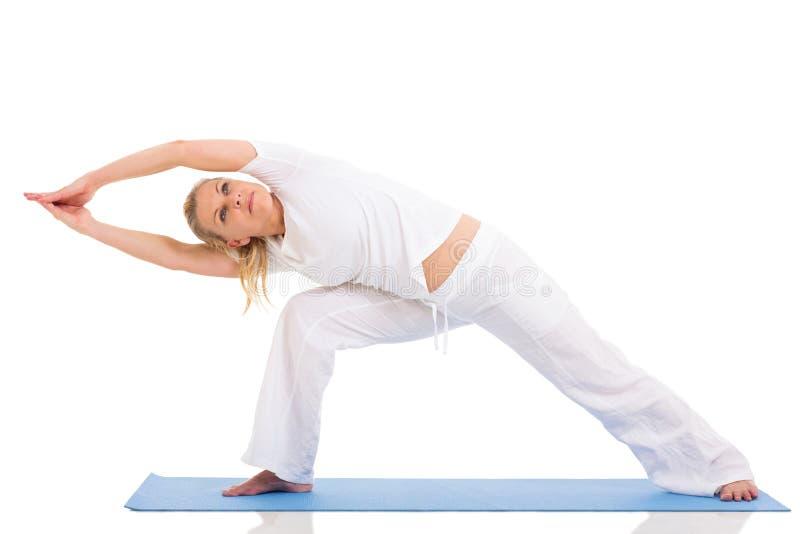 Mid age woman yoga. Flexible mid age woman doing yoga exercises isolated on white stock photo