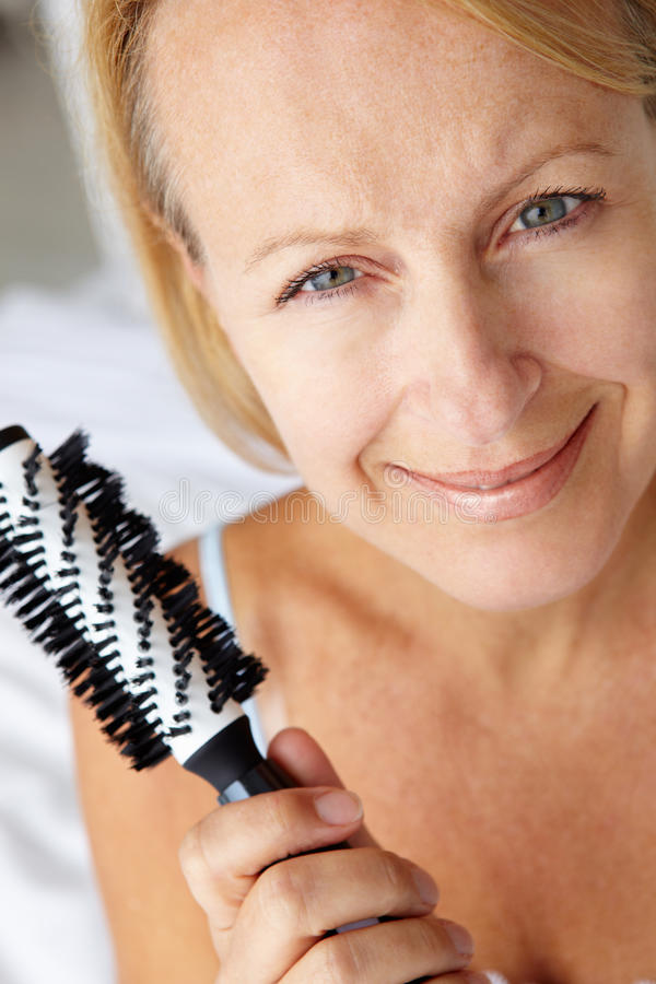 Download Mid Age Women Looking At Camera With A Hairbrush Stock Image - Image: 21013387