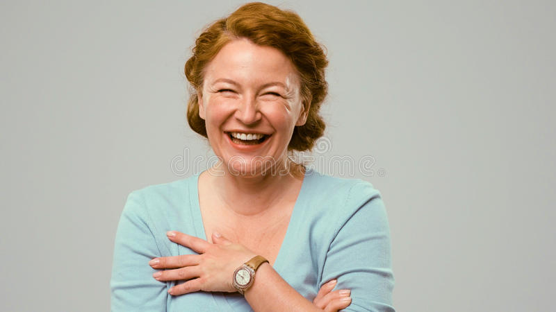 Mid aged actress showing emotions of happiness. Mid aged woman showing emotions of happiness. Close-up portrait of an actrees in light blue jumper. Actress with stock photo
