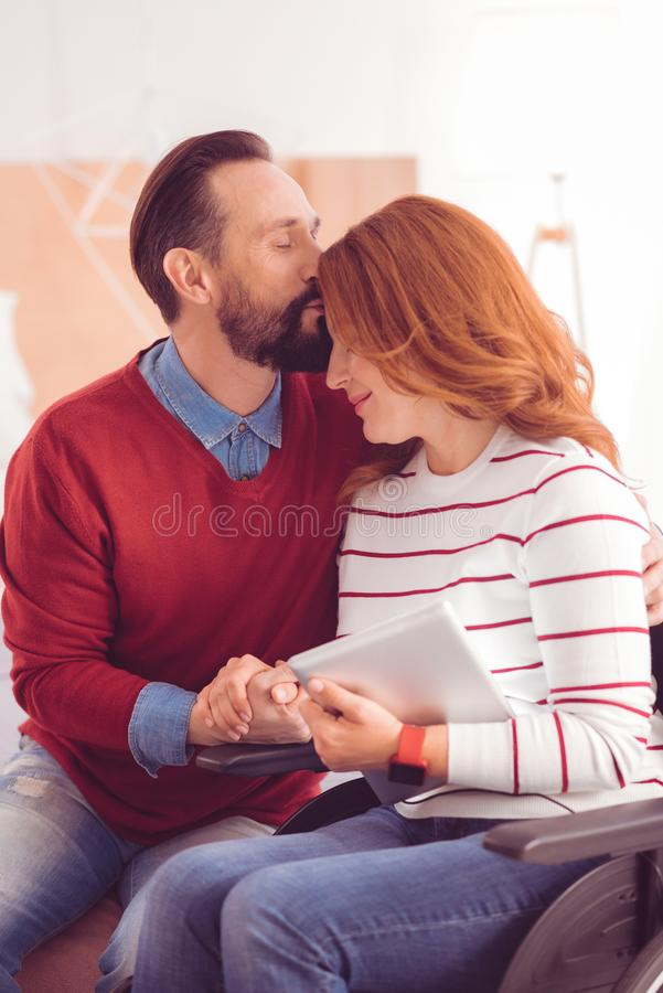 Mid aged loving man kissing a forehead of his immobile wife royalty free stock image
