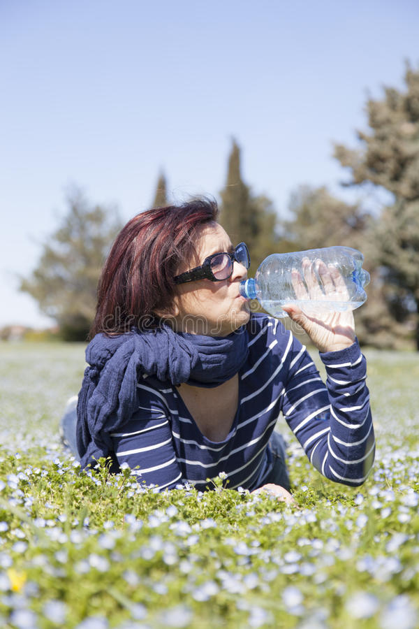 Download Mid Aged Woman Relaxing And Drinking Water On Grass Stock Photo - Image: 30107158