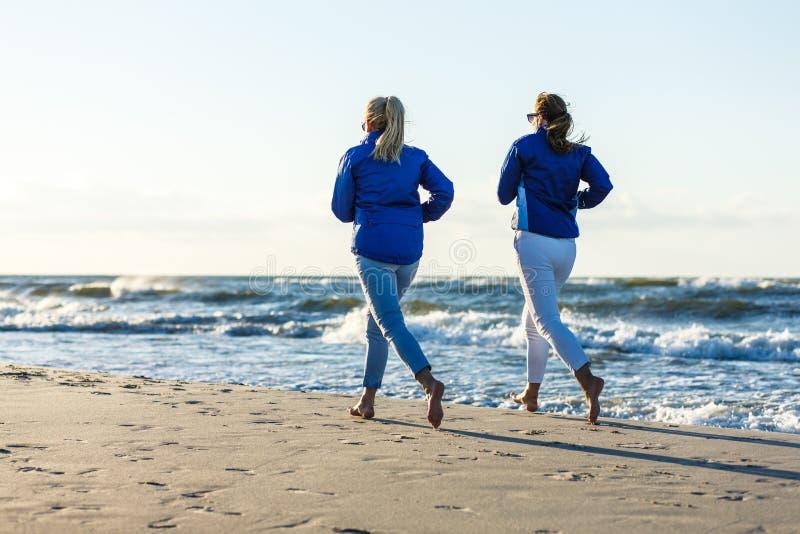 Mid aged women running on beach royalty free stock image