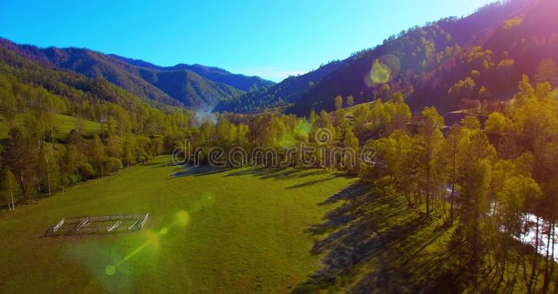 Mid air flight over fresh mountain river and meadow at sunny summer morning. Rural dirt road below. stock photography