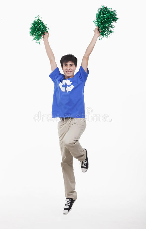 Mid-air shot of smiling young man with recycling t-shirt cheering with pompoms, studio shot stock image