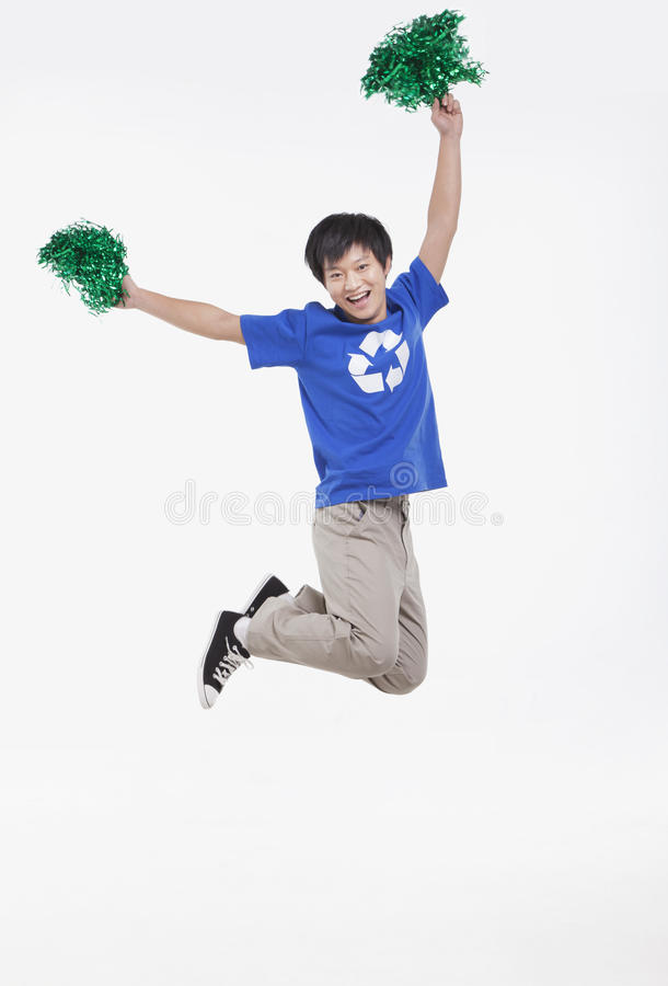 Mid-air shot of smiling young man with recycling t-shirt cheering with pompoms, studio shot stock photography