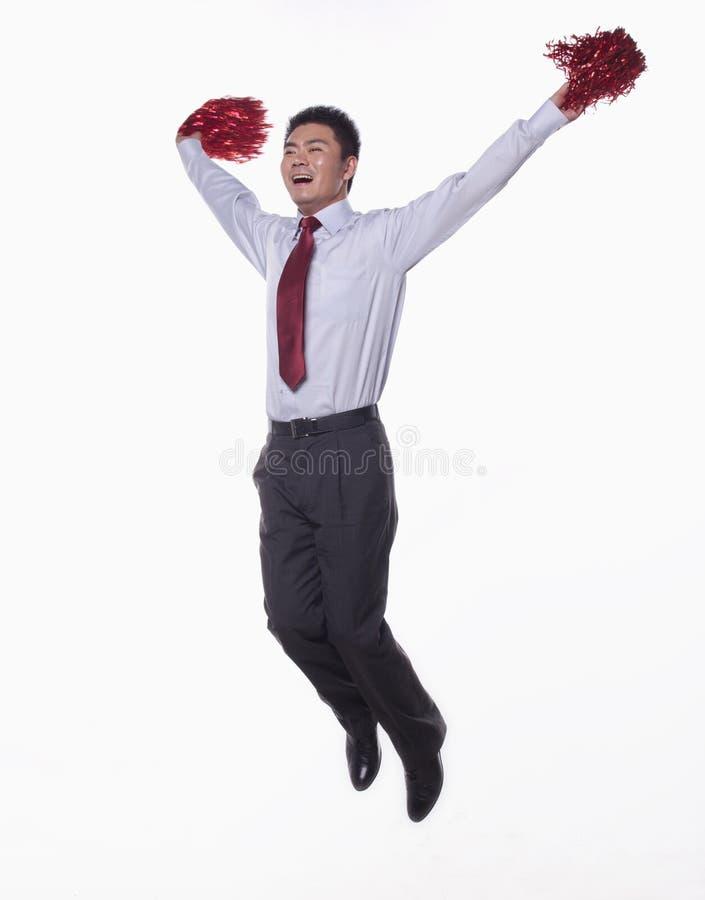 Mid Air van zakenman het springen en het toejuichen met pompoms in handen, studioschot wordt geschoten dat stock afbeelding