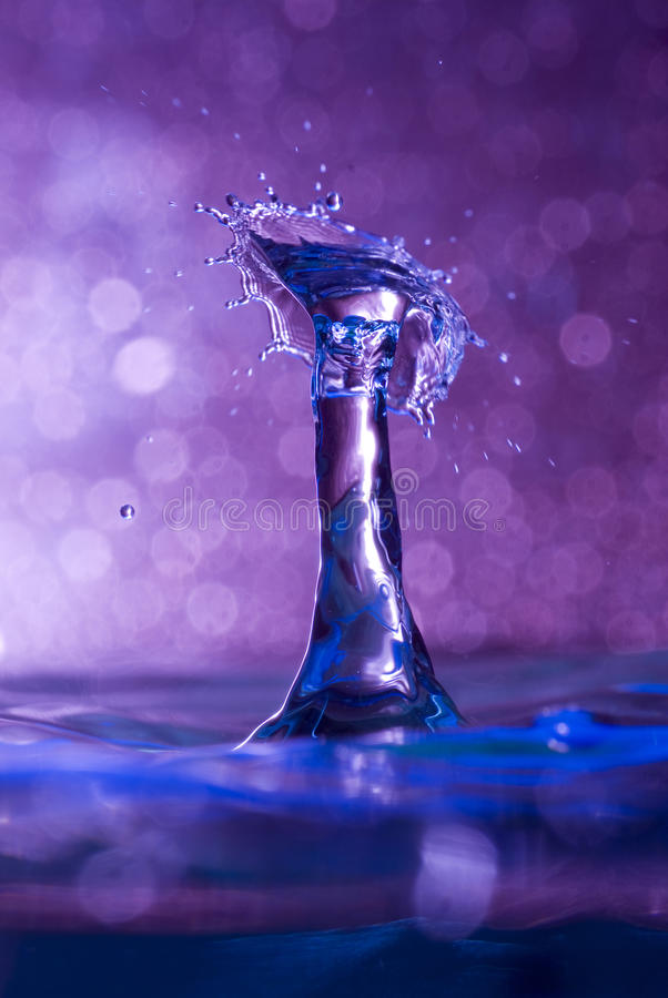 Mid air water drop and splash collision. Brightly coloured capture of a water drop collision royalty free stock photos