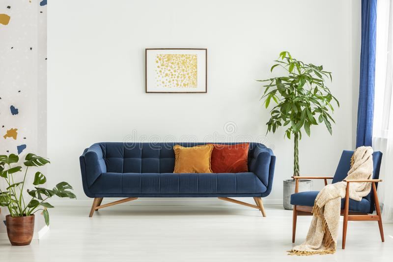 Mid-century modern chair with a blanket and a large sofa with colorful cushions in a spacious living room interior with green plan royalty free stock image