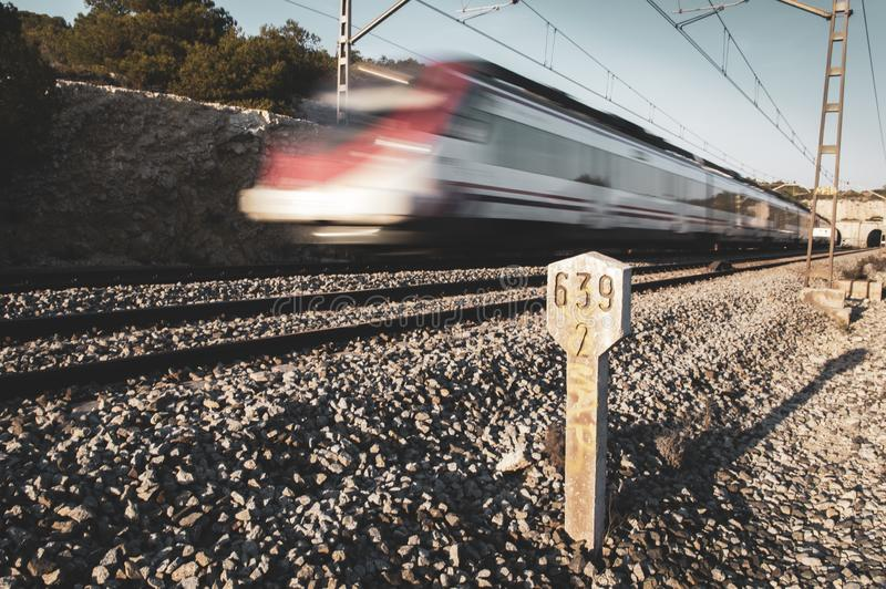 Mid-distance train moving out of a tunnel with the light in front of the sunset and kilometric railway signals along the tracks stock photos