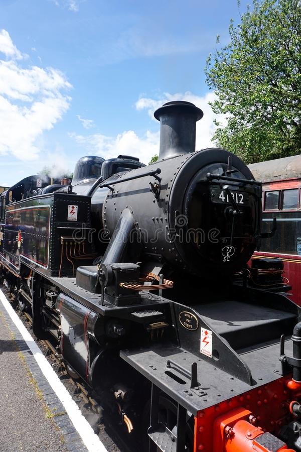 A steam train at a platform on the Mid Hants steam railway royalty free stock photo