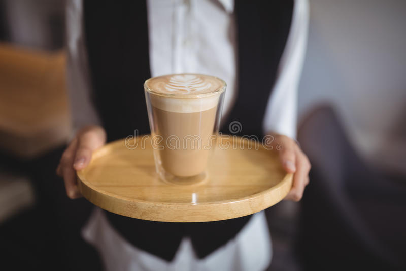 Mid-section του δίσκου εκμετάλλευσης σερβιτορών με το ποτήρι του καφέ στοκ φωτογραφία