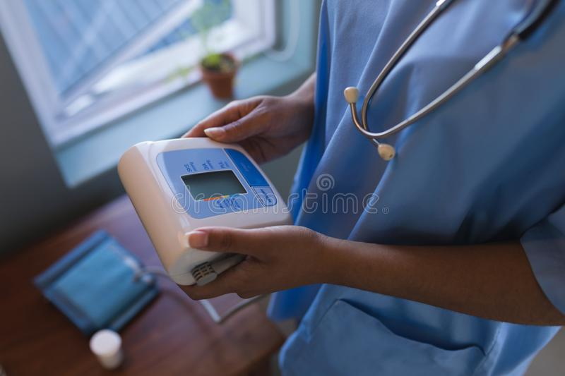 Female doctor holding blood pressure monitor at home stock photo