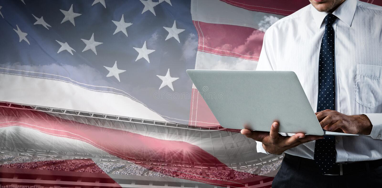 Composite image of mid-section of business man using a laptop stock photography
