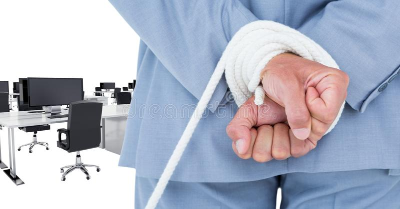 Mid section of businessman being tied up with rope in office royalty free stock photo