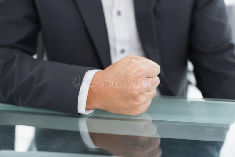 Mid section of businessman with clenched fist on office desk royalty free stock photography