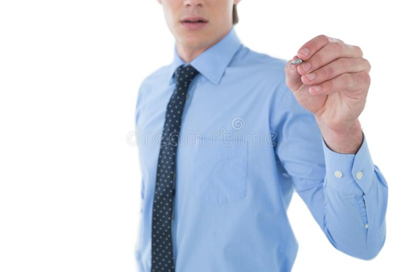 Mid section of businessman writing on imaginary screen. While standing against white background stock photography