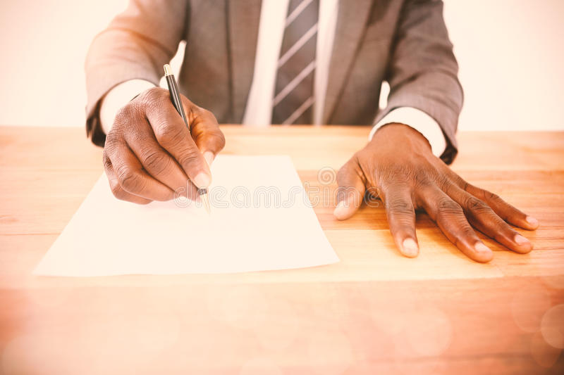 Mid section of businessman writing on paper stock photography