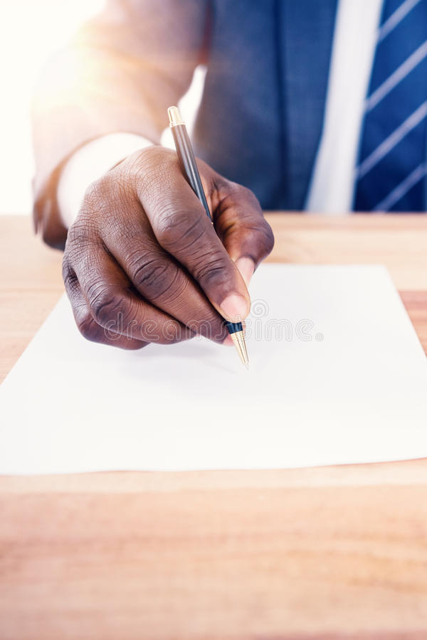Mid section of businessman writing on paper royalty free stock photo