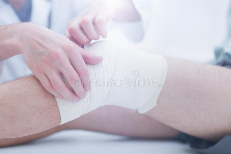 Mid section of doctor bandaging leg of patient in hospital royalty free stock image