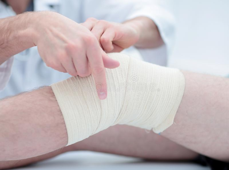 Mid section of doctor bandaging leg of patient in hospital stock image
