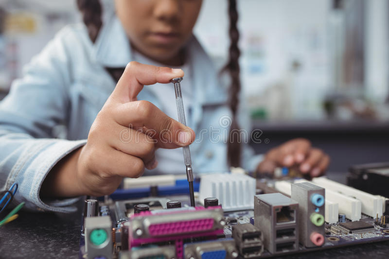 Mid section of elementary girl assembling circuit board. On desk at electronics lab royalty free stock photos