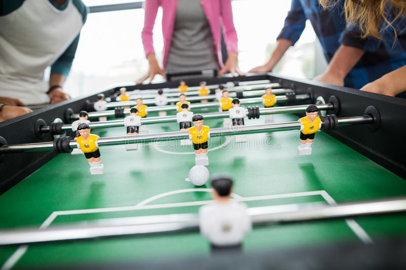 Mid section of executives playing table football stock photography