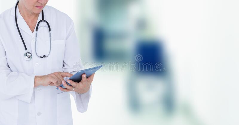 Mid section of female doctor using digital tablet in hospital. Mid section of female doctor wearing a lab coat and stethoscope using a digital tablet working in royalty free stock image
