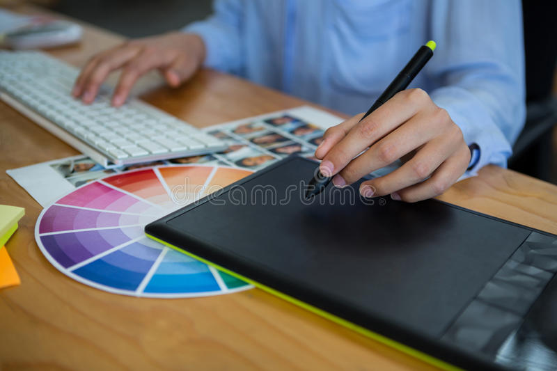 Mid section of female graphic designer using graphics tablet at desk royalty free stock images