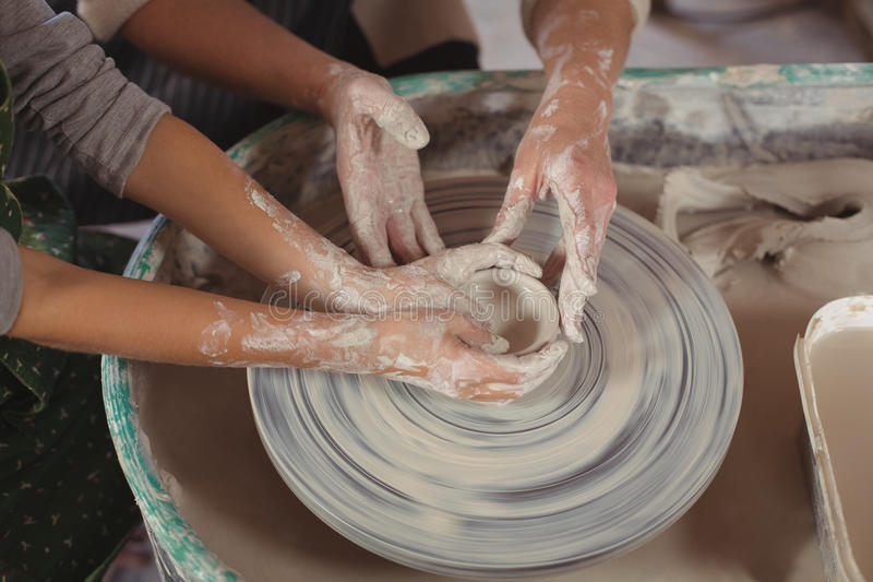 Mid section of female potter assisting girls. In pottery workshop royalty free stock photo