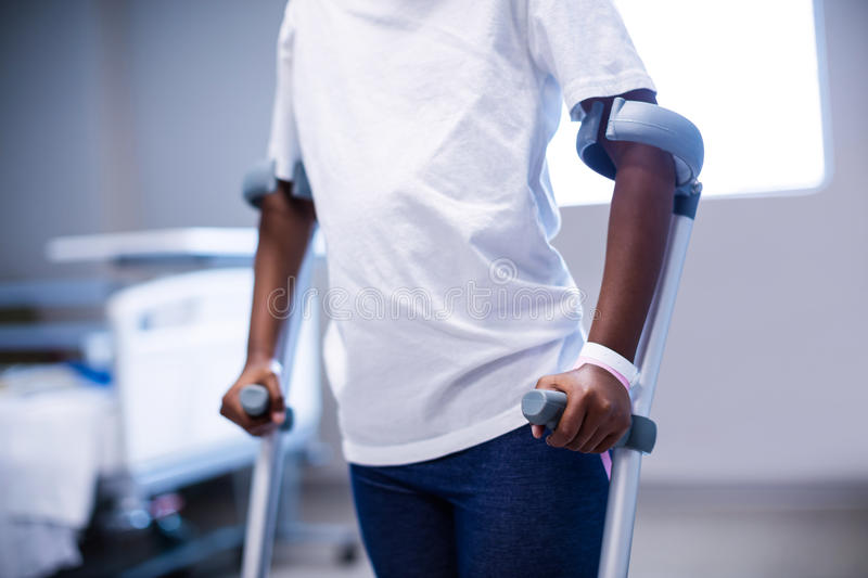 Mid section of girl walking with crutches in ward royalty free stock photo
