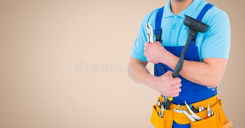 Mid section of handyman holding wrench and plunger with tool belt around his waist. Against beige background royalty free stock images
